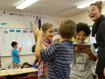 Students at Port Graham School test out their new iPads with teacher Devin Michel-Way. (Photo by Shahla Farzan/KBBI)