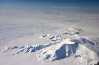This image taken in 2012 shows part of the Crosson Ice Shelf (center left) and Mount Murphy (foreground) on the western edge of Antarctica. Thwaites Ice Shelf lies beyond the highly fractured expanse of ice (center). (Photo by John Sonntag/Nature)