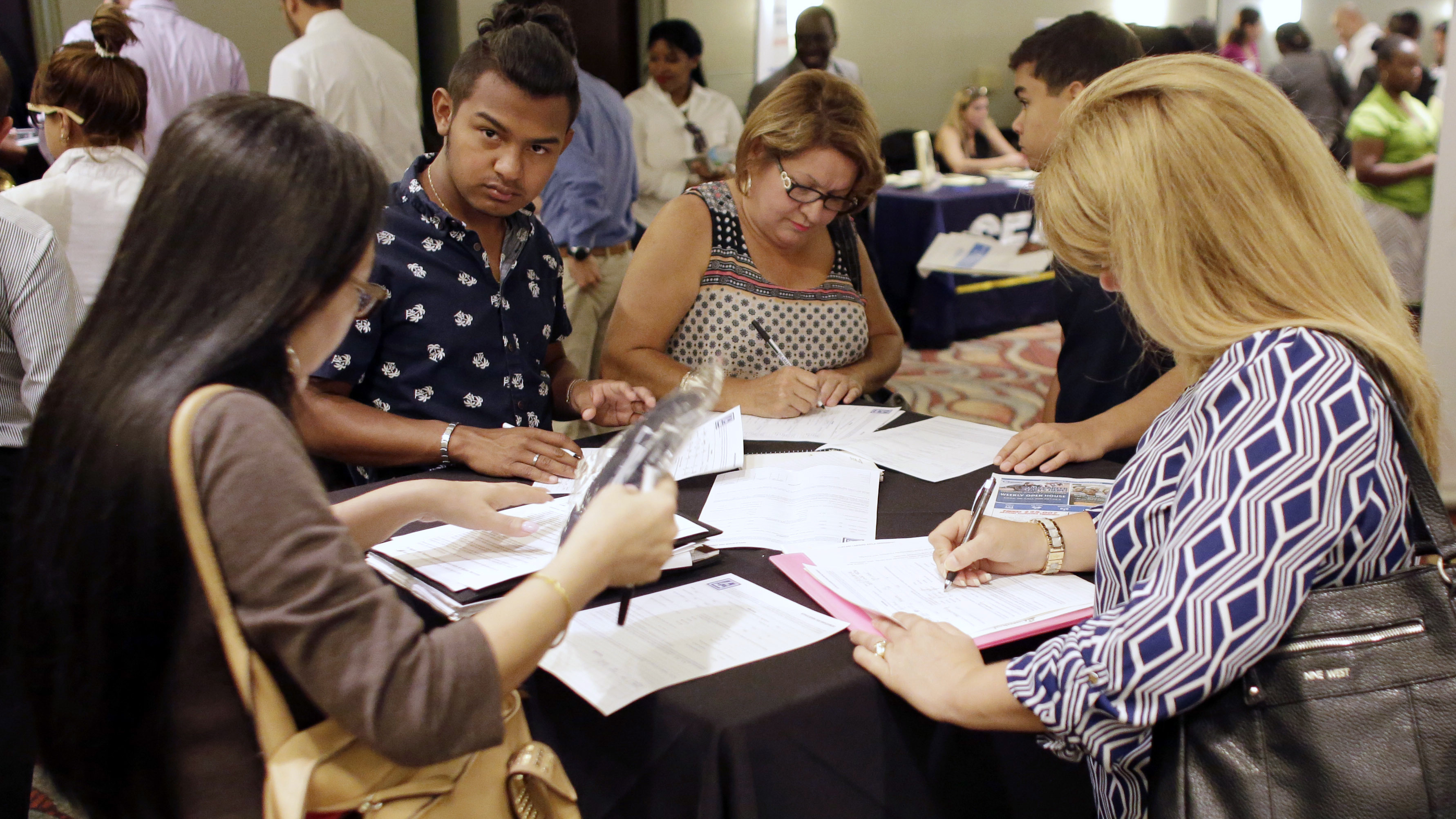 People fill out applications at a job fair in Miami Lakes, Fla., in July. The presidential candidates will be watching Friday's monthly Labor Department report for talking points on the unemployment rate and new and jobs.