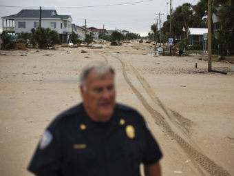 Chief of Police George Brothers walks along what used to be a four-lane national scenic byway that's now covered in sand after Hurricane Matthew hit the beach community of Edisto Beach, S.C., Saturday. David Goldman/AP
