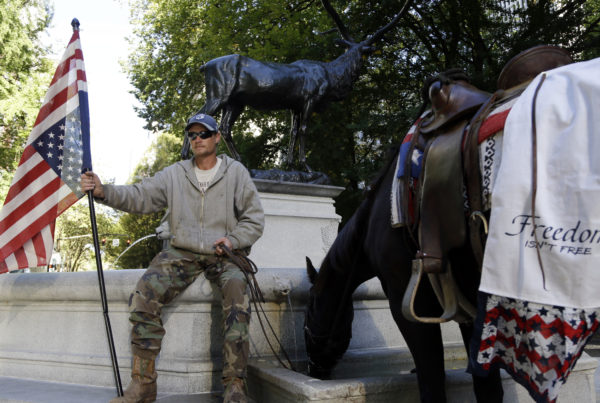 A protester, who would not identify himself, sits outside the federal courthouse in Portland as his horse, Lady Liberty, gets a drink from a fountain.