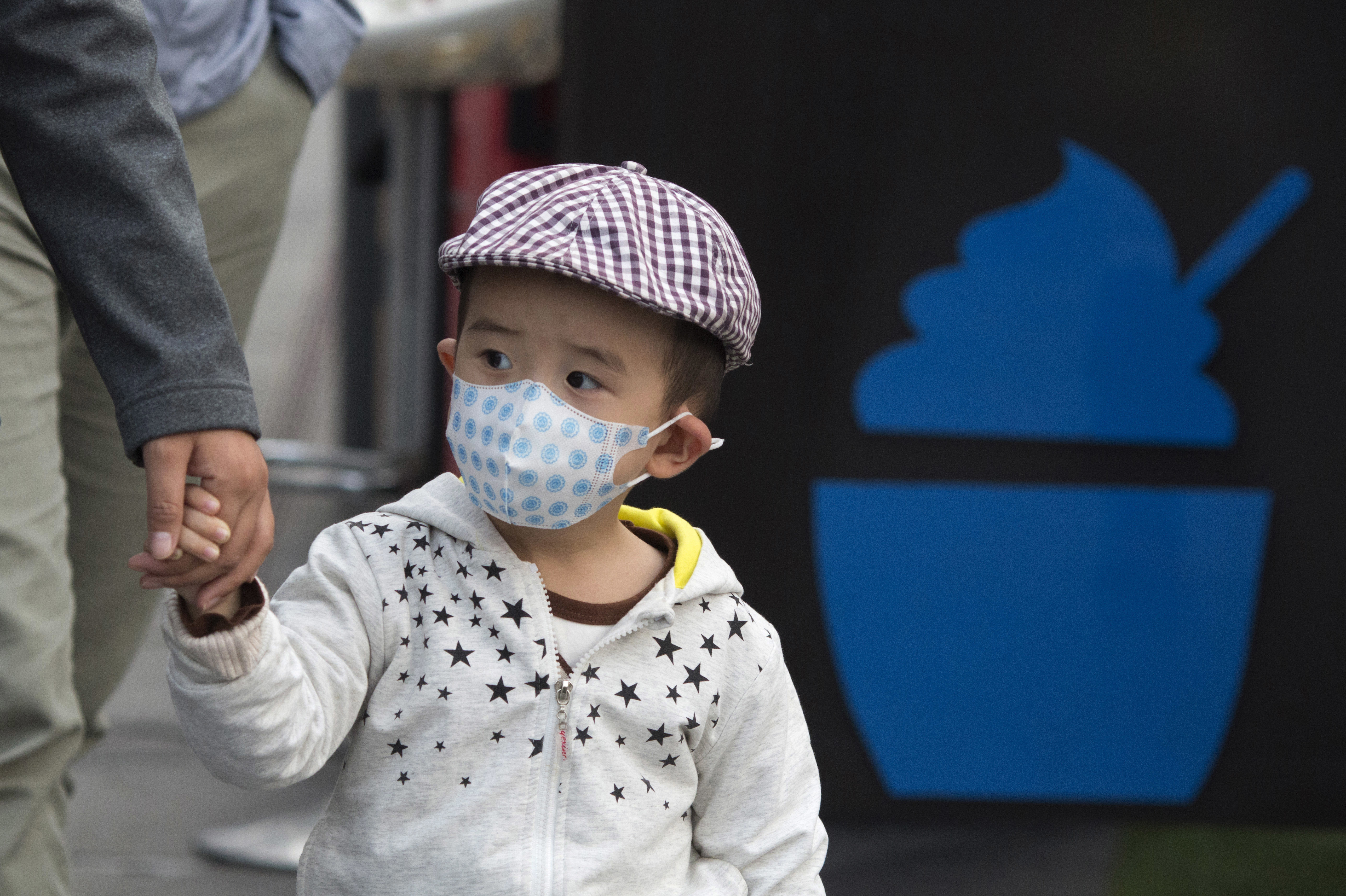 A child walks past a dessert stand on a hazy day in Beijing earlier this month.