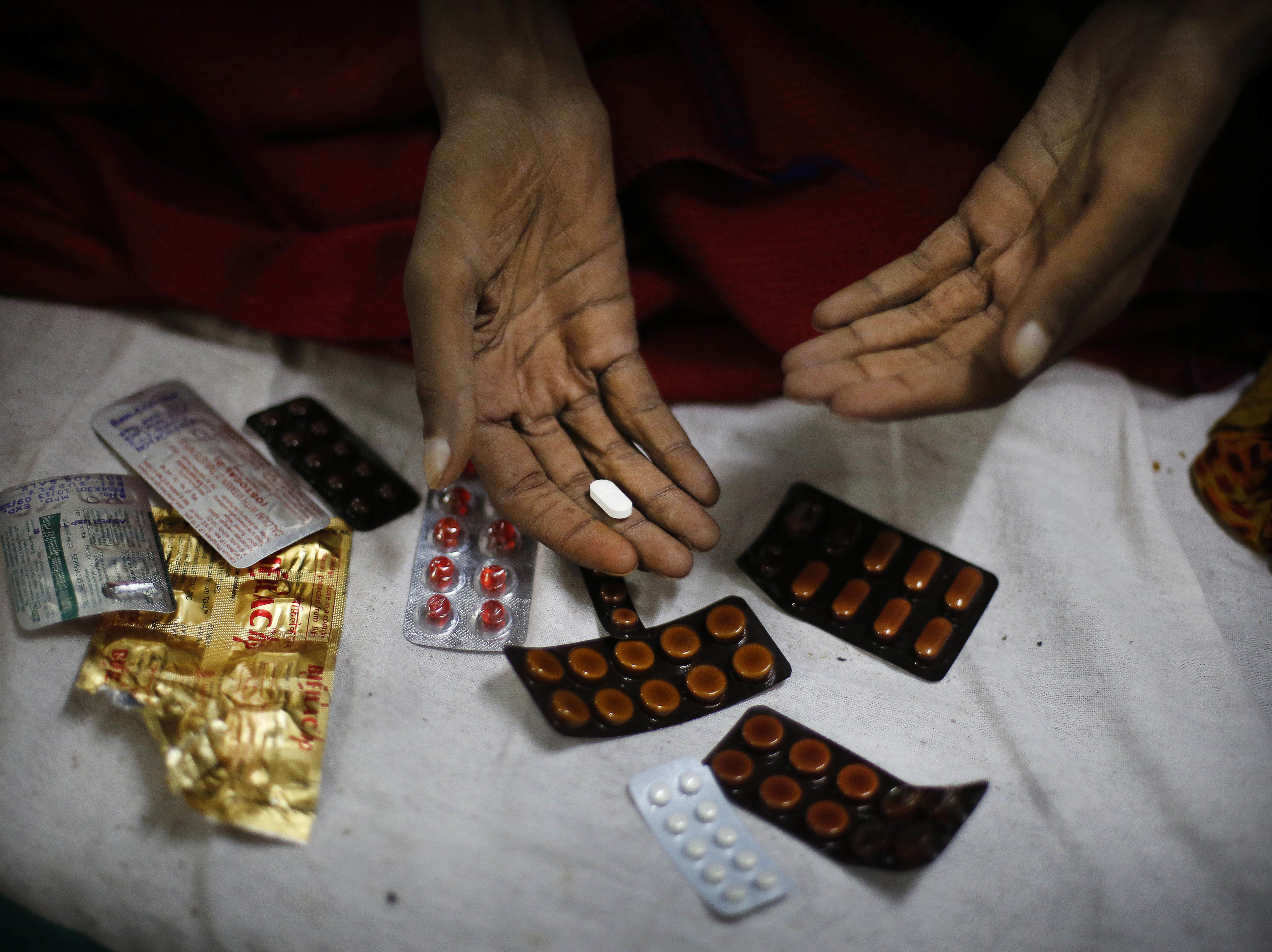 A 2014 photo shows a tuberculosis patient preparing to take his medication at Lal Bahadur Shastri Government Hospital in Varanasi, India.
