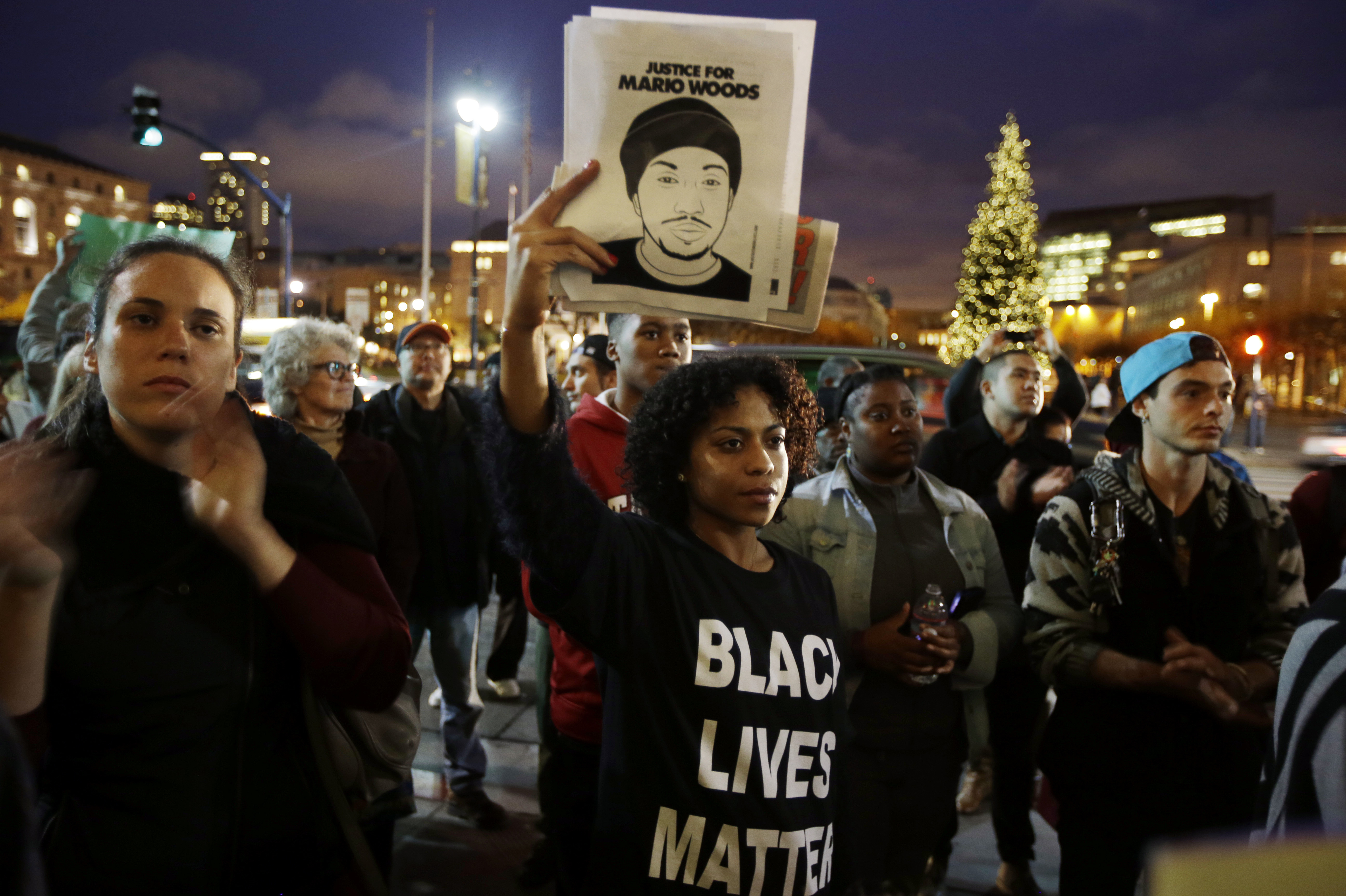 LaJoy Crenshaw, center, holds a picture of Mario Woods during a demonstration outside of city hall, in December 2015. (Photo by Marcio Jose Sanchez/Associated Press)