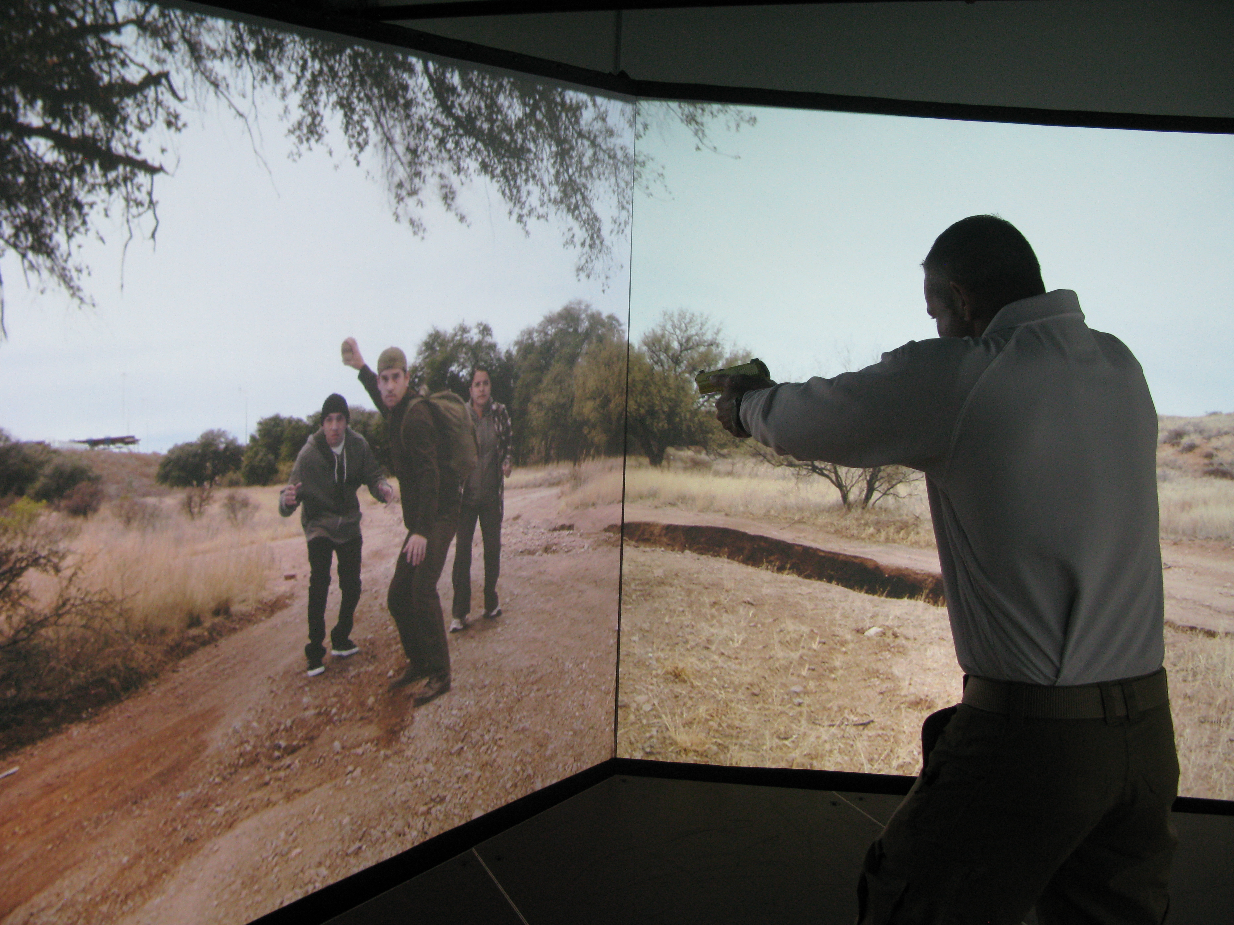 In order to reduce shootings, all Border Patrol agents are now required to train in a simulated environment complete with immigrants threatening rocks. Agent Aaron Sims trains on the simulator at the CBP National Training Center in Harper's Ferry, W.V. John Burnett/NPR