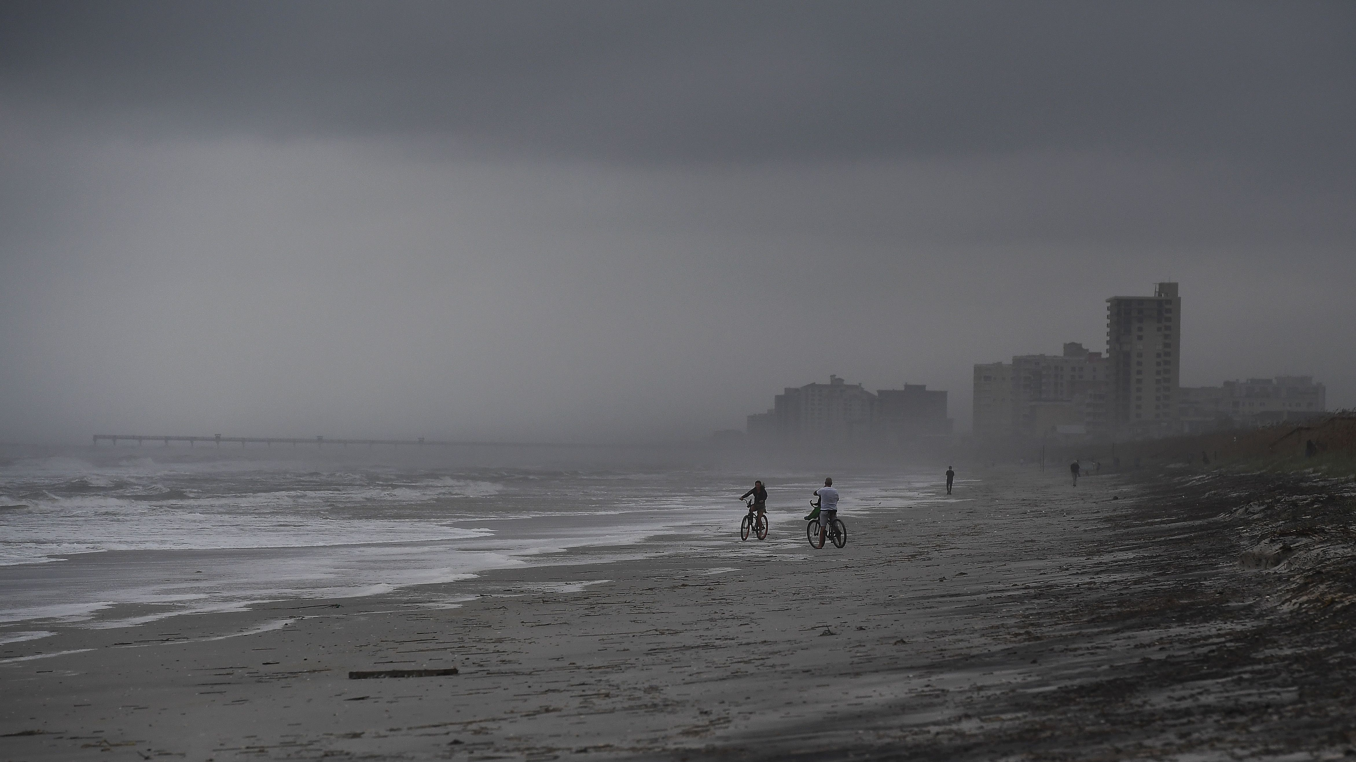 People bike on the beach ahead of Hurricane Matthew in Atlantic Beach, Fla., on Wednesday. Droves of people in the U.S. have begun evacuating coastal areas ahead of the storm, which tracked a deadly path through the Caribbean in a maelstrom of wind, mud and water. (Photo by Jewel Samad/AFP/Getty Images)