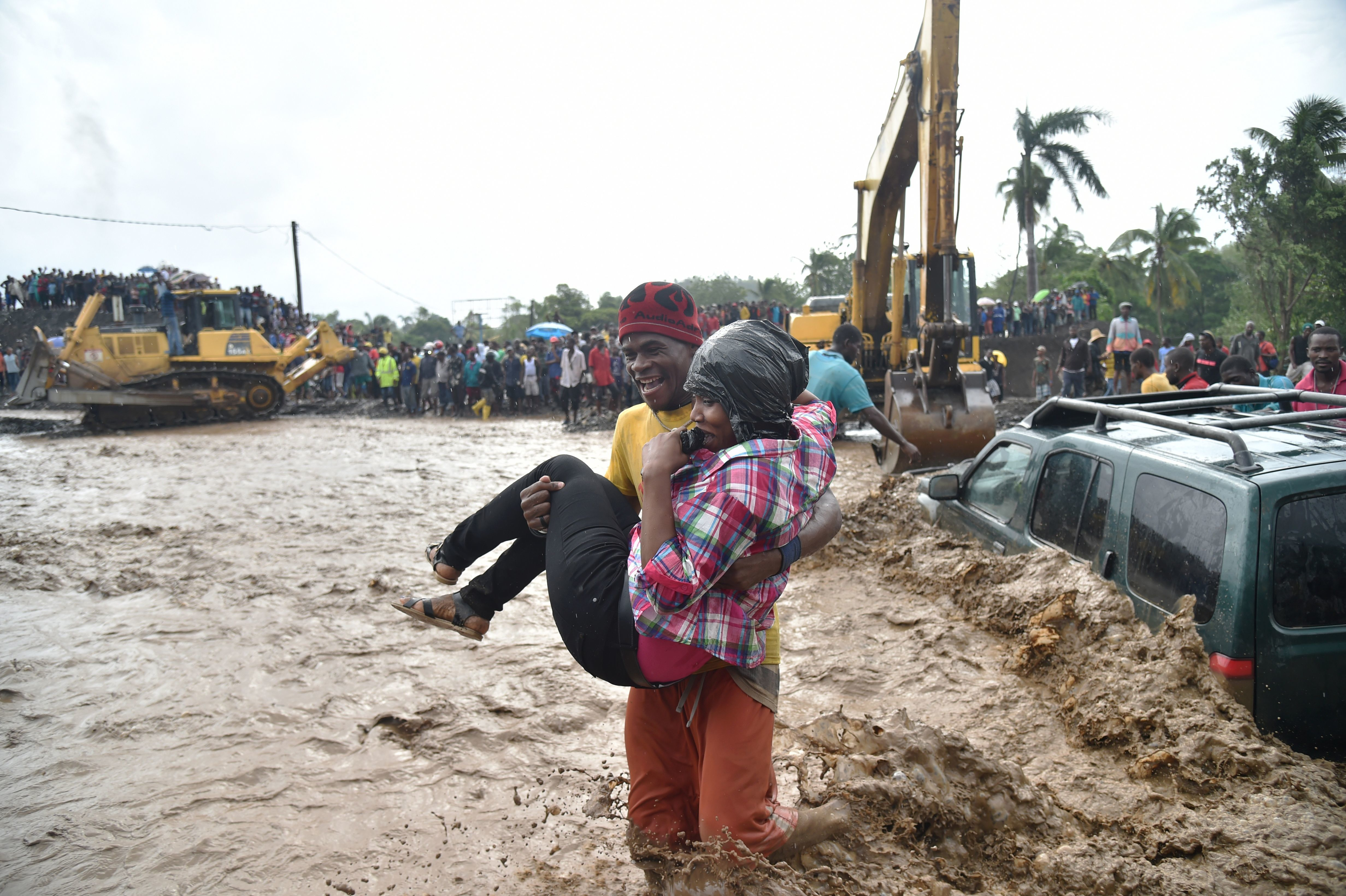 People help each other across the river La Digue in Petit Goave, Haiti, on Wednesday, a day after Hurricane Matthew raked the island nation. (Photo by Hector Retamal/AFP/Getty Images)