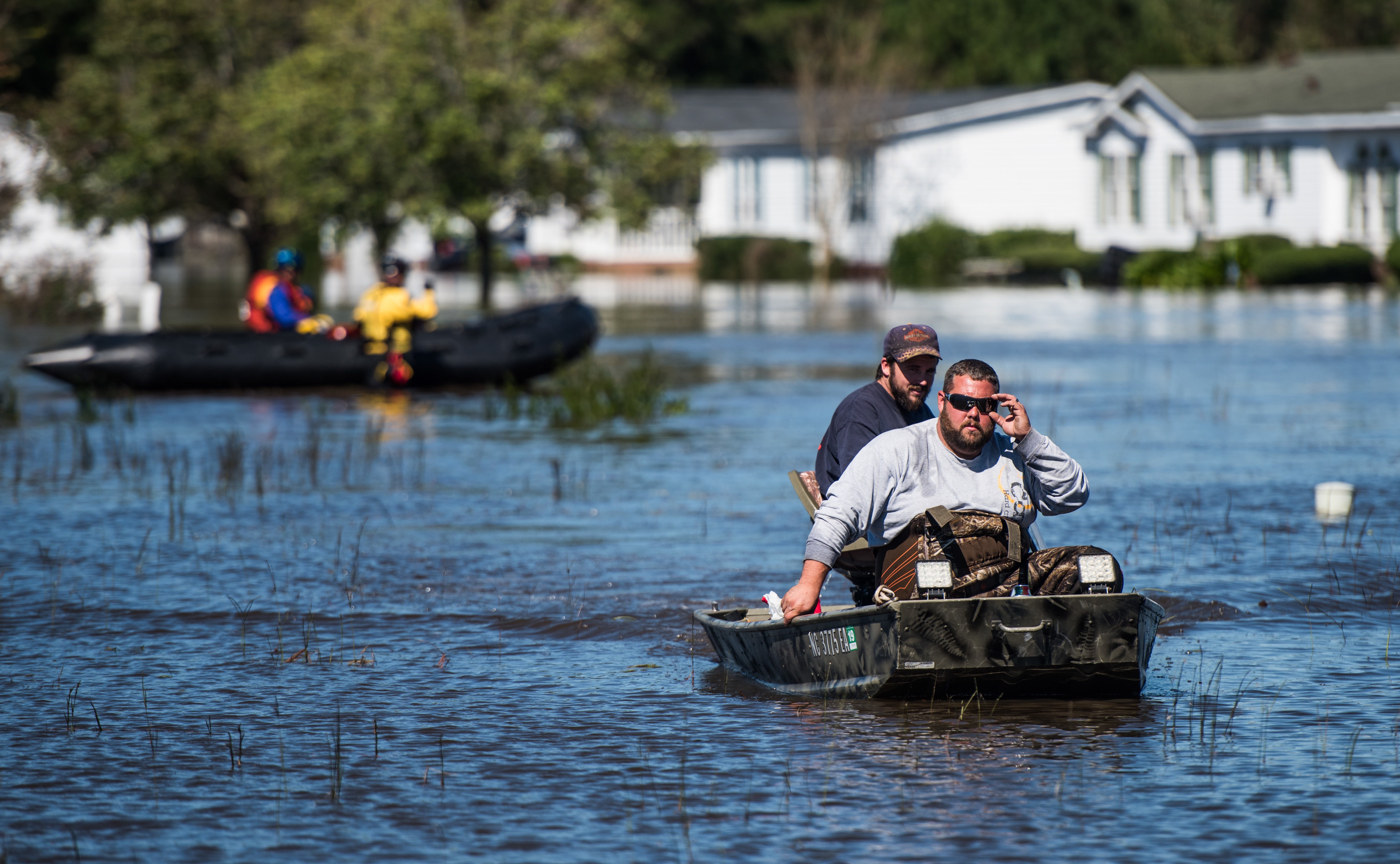 Residents and rescue teams navigate floodwaters in Lumberton on Monday. The U.S. death toll from Hurricane Matthew has climbed to more than 20 people.