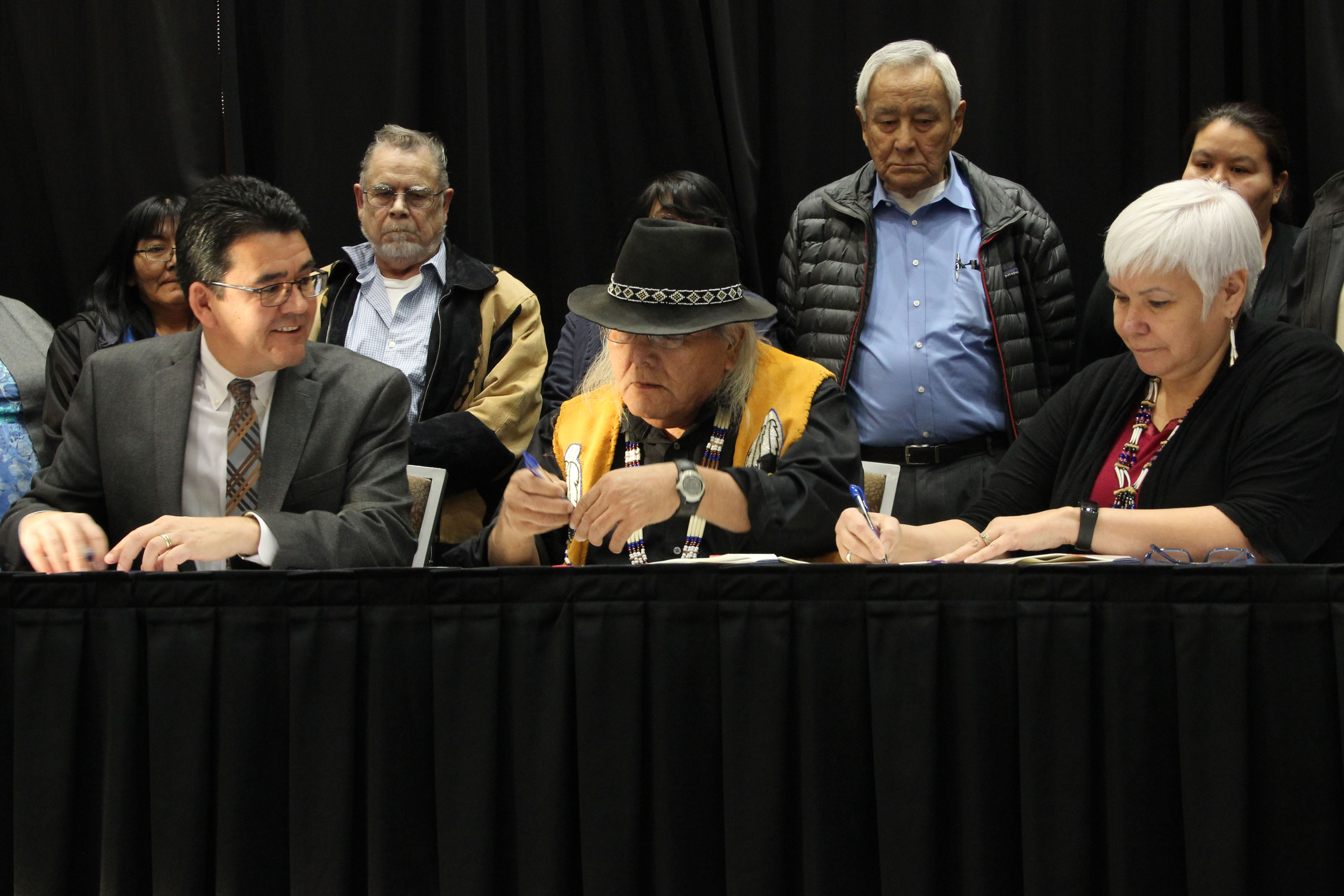 Deouty Interior Secretary Michael L. Connor joins Christopher Gene (center) and Karen Linnell of the Ahtna Intertribal Resource Commission to sign an agreement giving Alaska Native tribes in the Ahtna region more say over subsistence resources. (Photo by Rachel Waldholz/Alaska's Energy Desk)