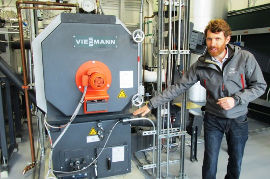 Andrew Haden of Wisewood, Inc., a Portland-based design firm, explains how the Ketchikan Airport's biomass boiler works last June. It was partially funded by a U.S. Forest Service wood innovation grant.  (Photo by Leila Kheiry/KRBD)