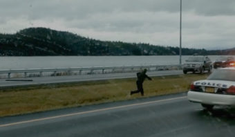 A Juneau Police Department officer in the median of Egan Drive dodges the vehicle barreling at him in this still from a video posted to Facebook by Richard Koddi Moe). The driver swerved at the officer, who was attempting to use a spike strip.