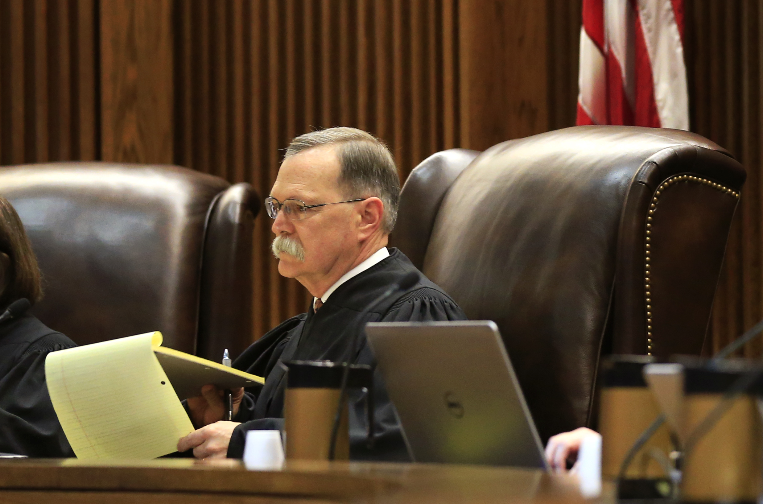 Chief Justice Lawton Nuss takes notes during arguments before the Kansas Supreme Court in Topeka, Kan., on Dec. 14, 2015. Nuss faces a retention election this year — and an unprecedented campaign to vote him out of office. Orlin Wagner/AP