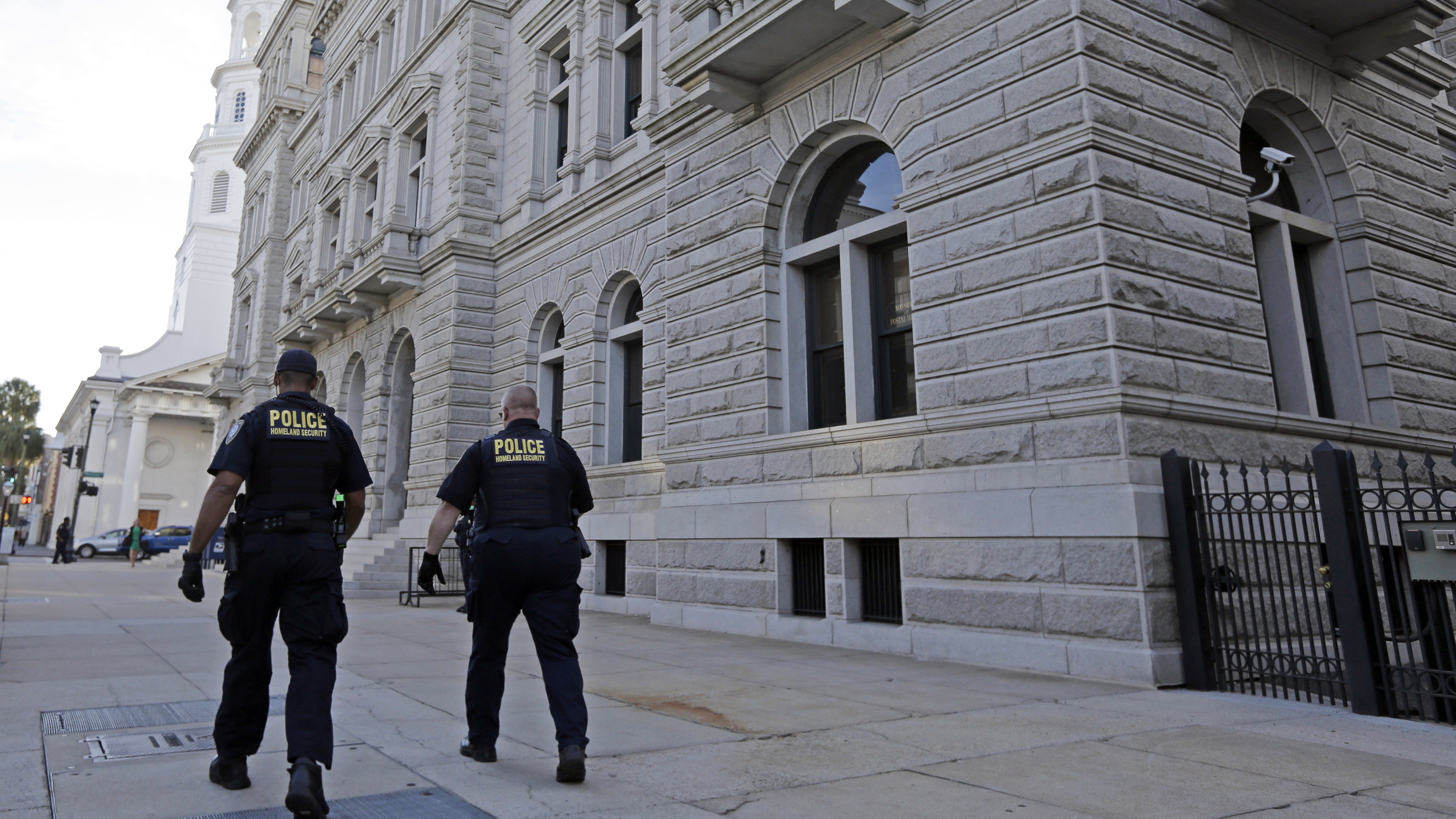 Homeland Security officers walk outside the federal courthouse in Charleston, S.C. Jury selection in the case will resume Monday.