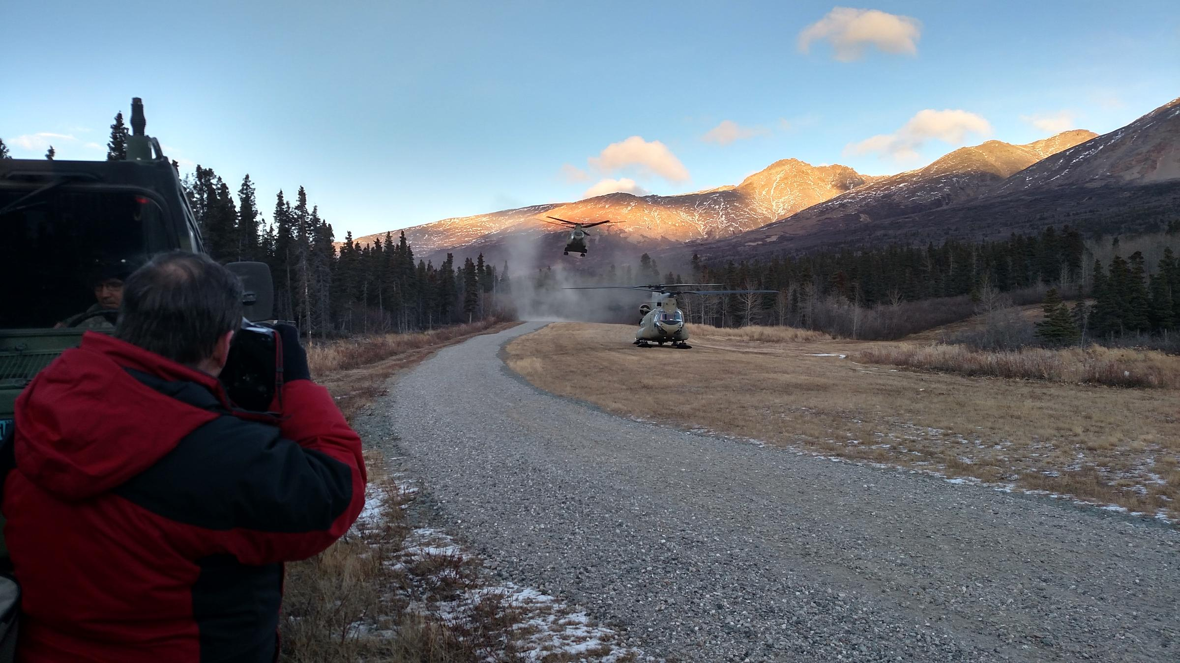 A second Chinook helicopter carrying U.S. and Canadian general/admiral-ranking officers and their staffs kicks up dust Tuesday upon landing at Black Rapids Training Site after a flight from Eielson Air Force Base. (Photo by Tim Ellis/KUAC)