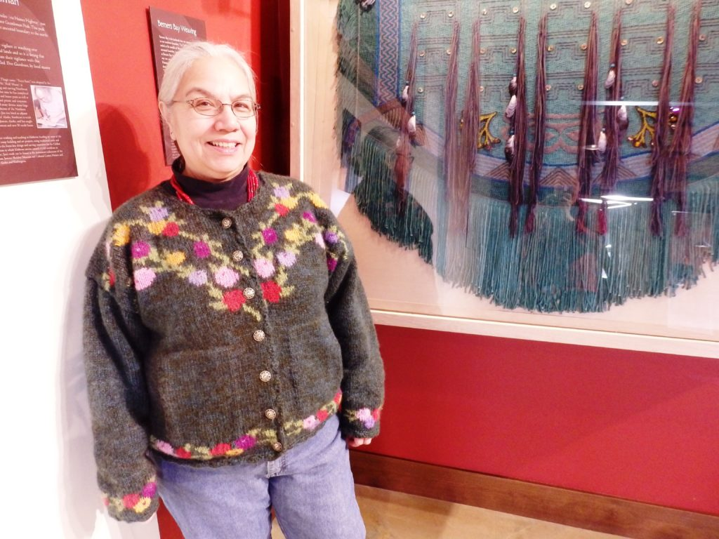 Lani Hotch, executive director of the Jilkaat Kwaan Heritage Center, stands next to her contemporary weaving that represents Berners Bay. (Photo by Emily Files/KHNS)