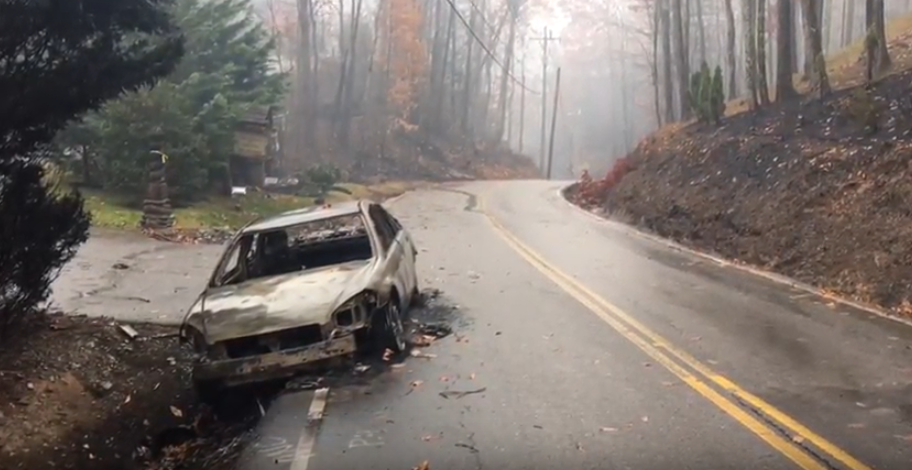 A burned-out car sits on the side of a road near Gatlinburg, Tenn. (Video screenshot from the Tennessee Department of Transportation)