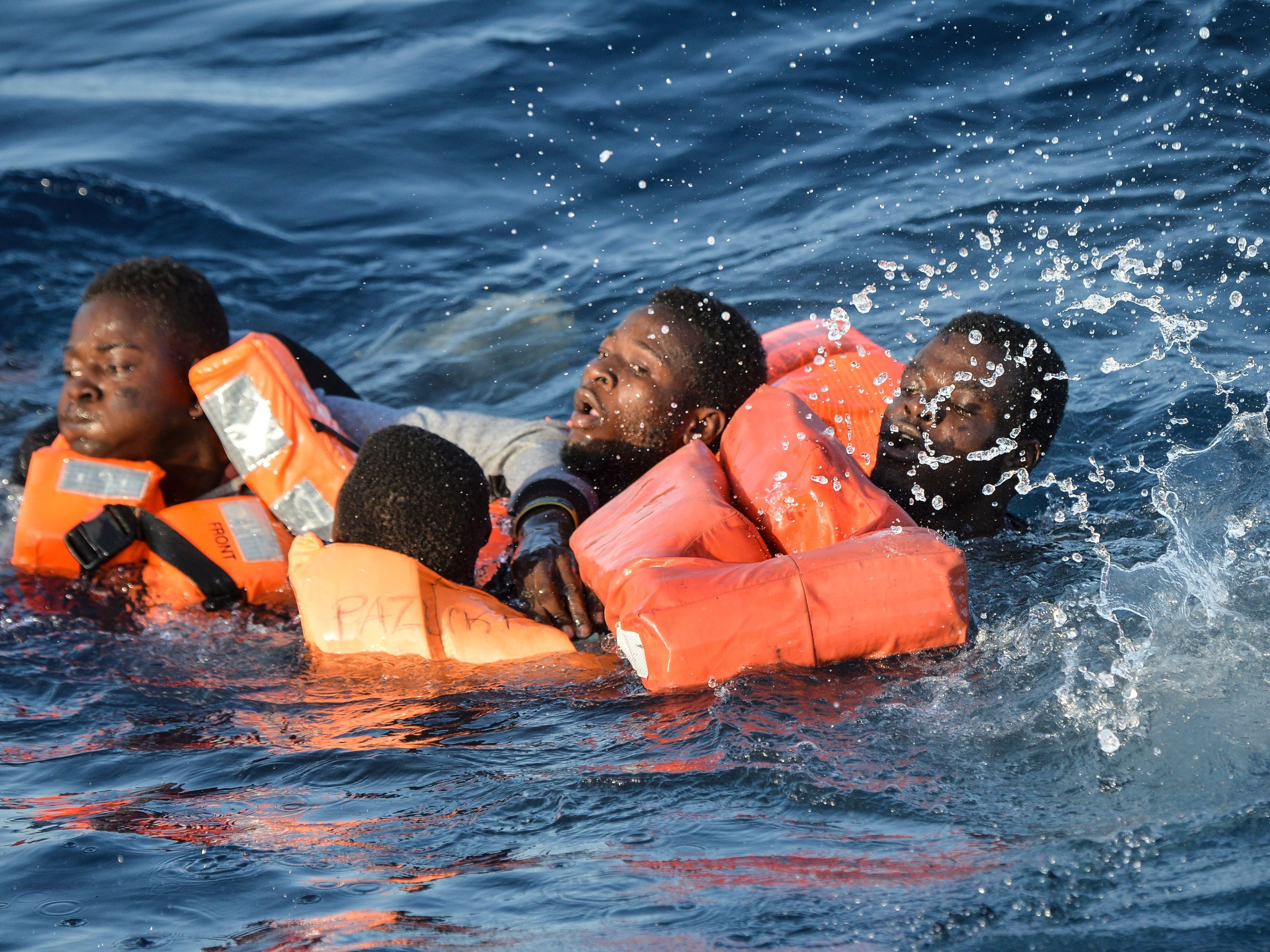 People struggle in the water during a rescue operation of a rescue ship run by Maltese NGO Moas and the Italian Red Cross off the Libyan coast.