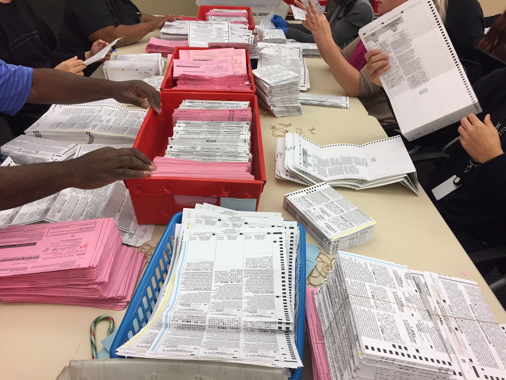 Election workers sort through unprocessed vote-by-mail ballots at the Sacramento County Registrar of Voters office on Monday. (Photo by Ben Adler/Capital Public Radio)