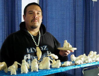 Dennis Pungowiyi shows off one of his favorite carving motifs, a mother walrus with her pup. (Photo by Zachariah Hughes/Alaska Public Media)