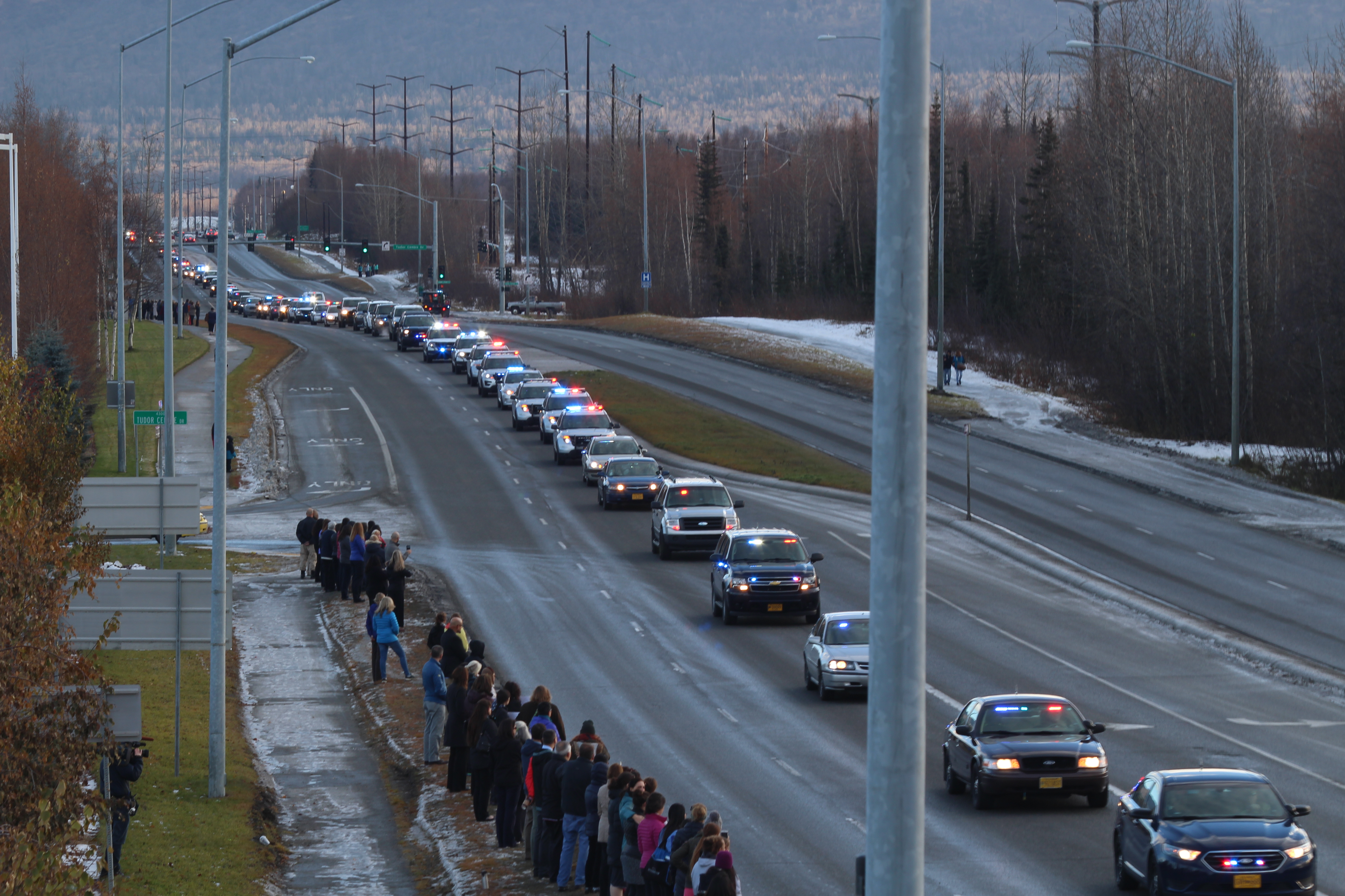 Anchorage citizens watch as a police escort brings FPD Sgt. Allen Brandt's body to Ted Stevens International Airport for transport to Fairbanks (Photo by Wesley Early, Alaska Public Media – Anchorage)