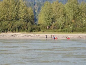 Kayakers rest near the U.S.-Canadian border on the Stikine River, marked by a line of cleared trees. (File photo by KFSK)