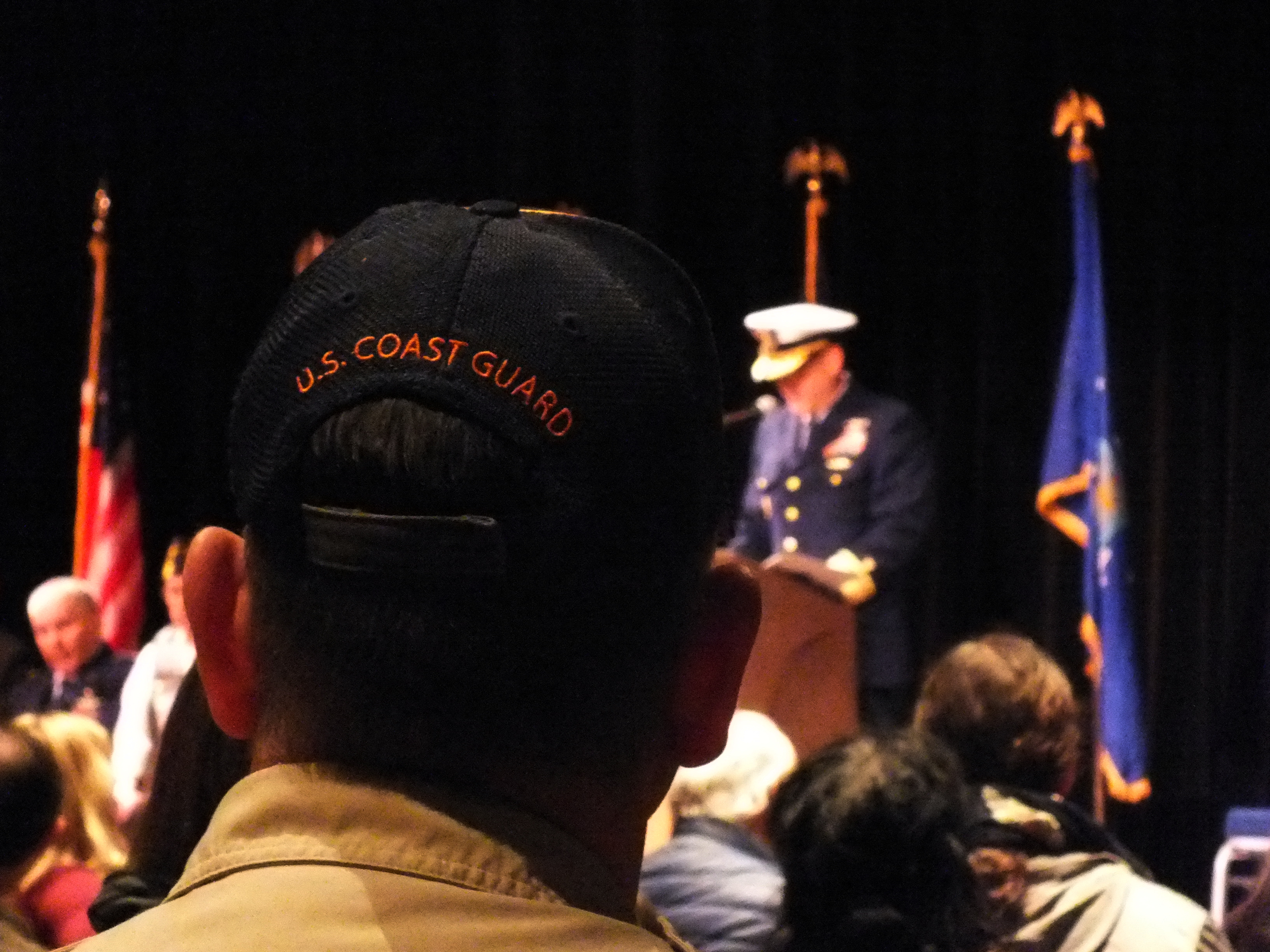 A Boy Scout troop leader, wearing a cap with U.S. Coast Guard embroidered on the back, listens as Rear Adm. Michael McAllister, commander of the U.S. Coast Guard's 17th District, speaks during Friday's Veterans Day observance at Centennial Hall.