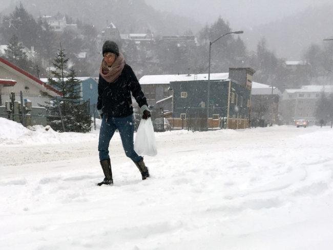 A pedestrian walks through a snowstorm  on Dec. 7, 2016 in Juneau, Alaska. (Photo by Rashah McChesney/Alaska's Energy Desk)