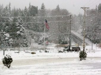A city snow plow tries to keep up with the heavy snowfall in this photo from a few winters ago. (File photo by KRBD)
