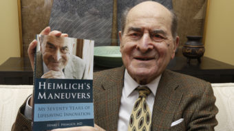 Dr. Henry Heimlich has died in Ohio at age 96. He's seen here in 2014, holding a copy of his memoir at his home in Cincinnati. Al Behrman/AP