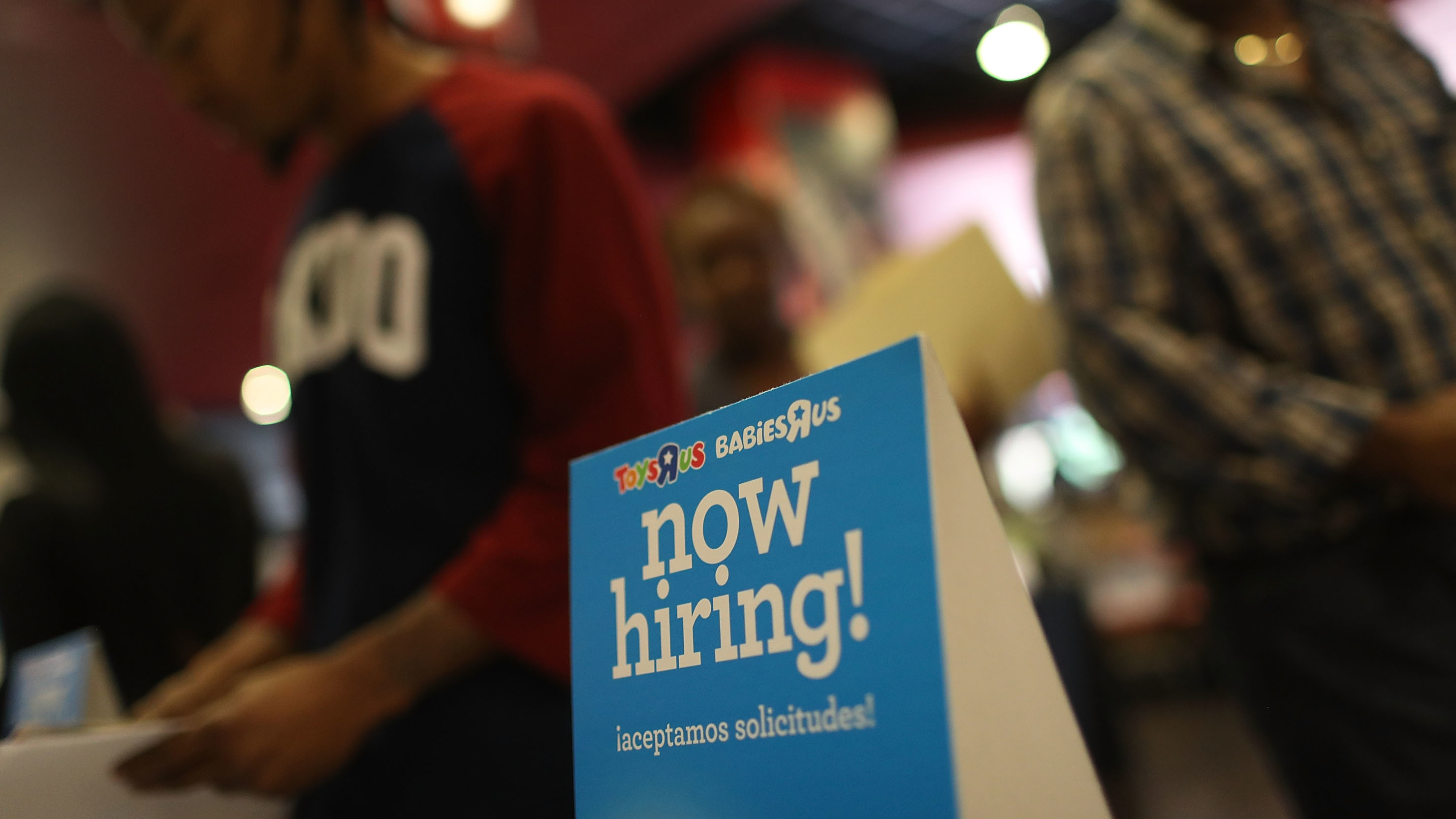 "A ""now hiring"" sign is seen at the Toys R Us booth during the JobNewsUSA job fair Nov. 15 at the BB&T Center in Sunrise, Fla."