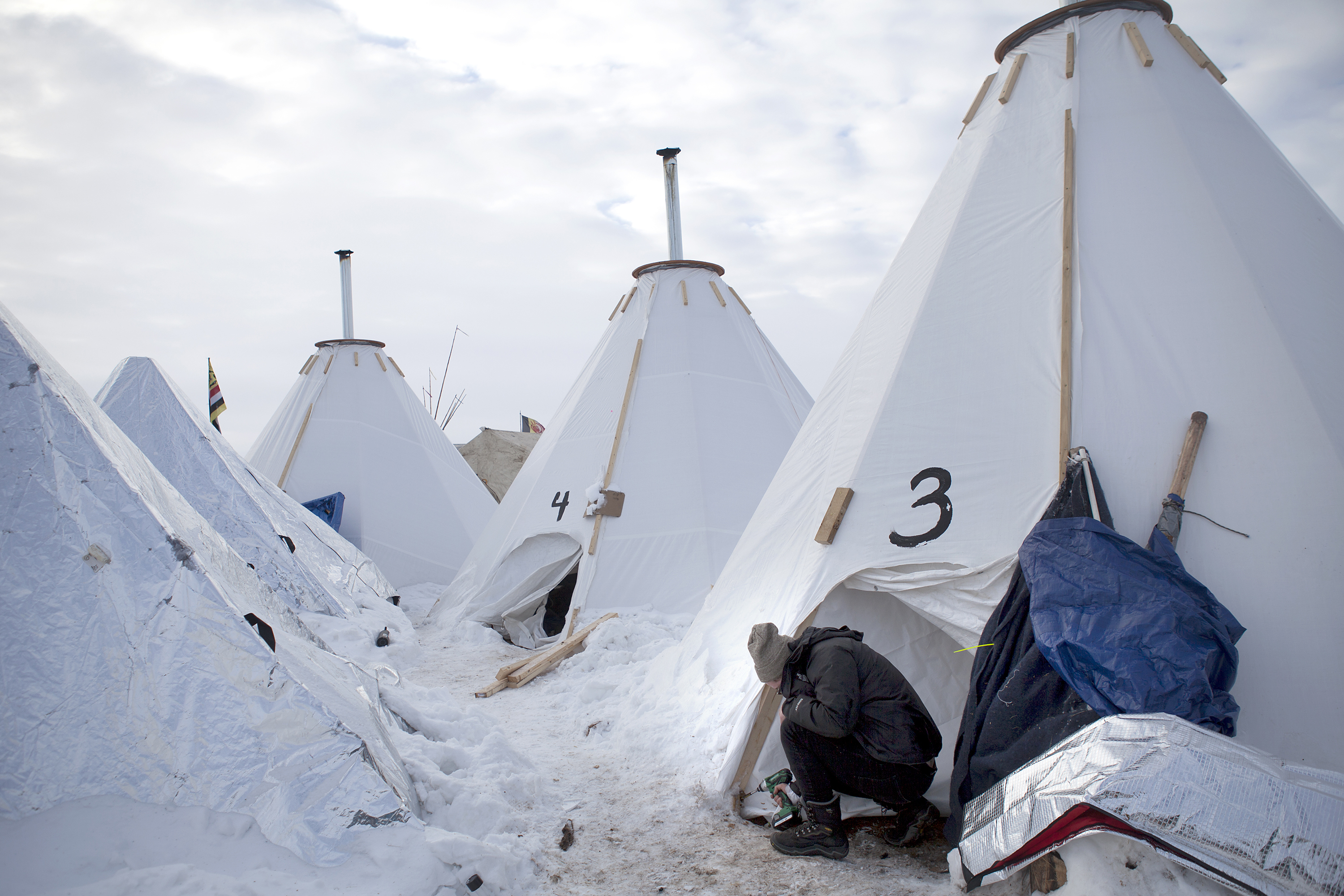 "Jacob Brooks makes adjustments to one of the camp's many ""tarpees,"" a winterized teepee made of tarp with a built-in chimney, designed by Paul Cheokoten Wagner. There are roughly 60 tarpees around various camps now, and Wagner has fundraised enough for another 20 more. Celia Talbot Tobin for NPR"