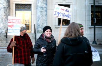 Protesters chat Monday morning, Jan. 30, 2017, in front of the Alaska State Capitol Building in downtown Juneau, Alaska. Protest organizers Jill Weitz and Dan Kirkwood estimate that about 175 people stood at the steps to support refugees and immigrants in the wake of President Donald Trump's executive orders heavily restricting immigration. (Photo by Tripp J Crouse/KTOO)