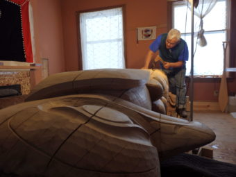 Wayne Price works on a 12 foot tall totem pole in his Haines studio. (Photo by Emily Files/KHNS)