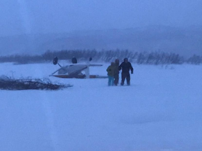 Three people walk away after their Cessna 180 crashed near a ridgeline landing strip in the vicinity of the Chakachatna River in the Kenai Peninsula, Alaska, Jan. 30, 2017. A Coast Guard Air Station Kodiak MH-60T Jayhawk crew transported the three to Anchorage International Airport. (Photo by U.S. Coast Guard)