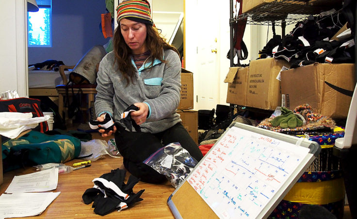 Kristin Bacon charts race strategies, packs drop bags, and diagrams which dogs will be run in an apartment on the Husky Homestead property outside Denali. (Photo by Zachariah Hughes/Alaska Public Media)