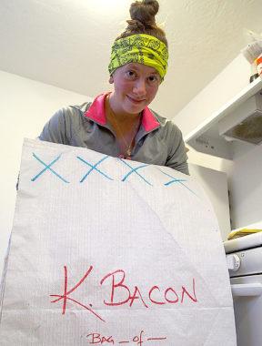 Tara Cicatello holds a drop bag she's helping prepare for Kristin Bacon. (Photo by Zachariah Hughes/Alaska Public Media)