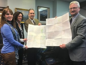 Sen. Natasha von Imhof, Kevin Gallagher, Ed Fogels hold new topographic maps of Alaska created through the Alaska Mapping Initiative.