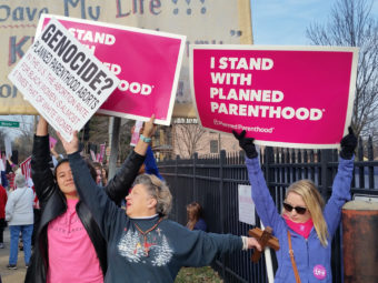 Planned Parenthood supporters and an opponent of the organization try to block each other's signs during a protest and counterprotest Saturday in St. Louis. Jim Salter/AP