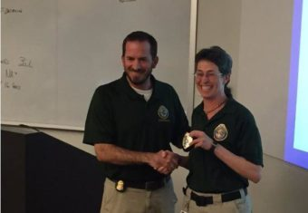FBI counselor Michael Siegling presents Unalaska's Jennifer Shockley with her new deputy police chief badge at the FBI National Academy in Virginia. (Photo by CREDIT FBI National Academy)