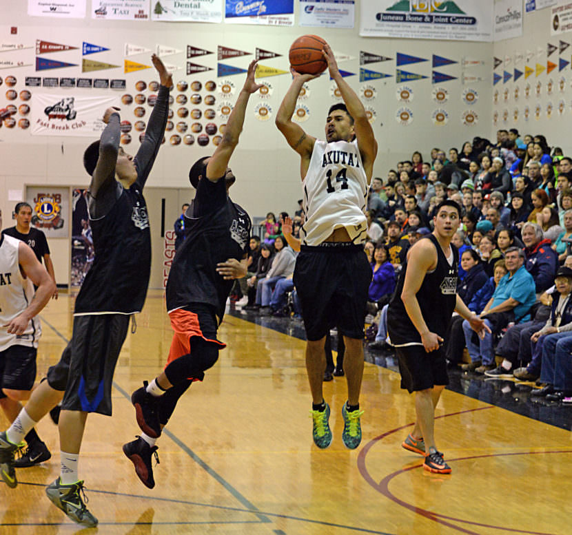 Yakutat's Martin Sensmeier (14) shoots over Angoon defenders during their B Bracket elimination game at the Juneau Lions Club 69th Gold Medal Basketball Tournament in 2015.