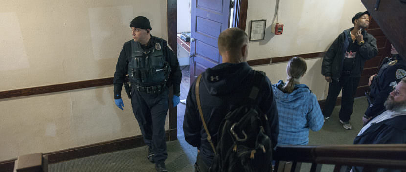 Juneau police and community members look on as residents of the Bergmann Hotel hurriedly packed their belongings and left their rooms on Friday March 10, 2017 in Juneau, Alaska. The building has been condemned and residents were given 24-hours to leave. (Photo by Rashah McChesney/Alaska's Energy Desk)