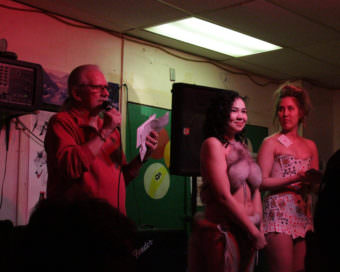 An MC at the Make Your Own Bikini contest at Nome's Polar Bar, announcing the year's winner and runner up (Photo – Zachariah Hughes, Alaska Public Media)
