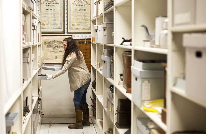 Jodi DeBruyne, curator of collections and exhibits for Juneau-Douglas City Museum, pulls items from the museums collections on April 14, 2017. (Photo by Tripp J Crouse/KTOO)