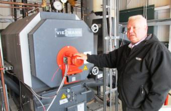 Airport Manager Mike Carney stands next to the Ketchikan International Airport's new biomass wood-pellet boiler last summer. (File photo by Leila Kheiry/KRBD)
