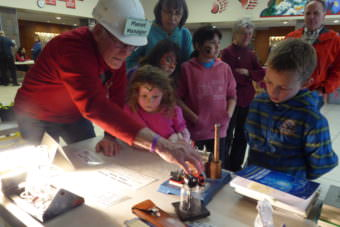 Bill Leighty, the Planet Manager shows a group of kids his model steam engine at the Juneau Renewable Fair in the JDHS commons on Earth Day.
