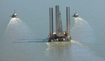 Tugs pull the Spartan 151 jack-up drilling platform up Cook Inlet in August 2011. Furie Operating Alaska, formerly Escopeta Oil, expects to be drilling again in the spring. (Photo courtesy Peninsula Clarion)