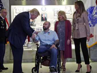 President Donald Trump shakes hands with U.S. Army Sgt. First Class Alvaro Barrientos, after awarding him with a Purple Heart , as first lady Melania Trump, right, stands with Tammy Barrientos second from right, at Walter Reed National Military Medical Center, Saturday. Alex Brandon/AP