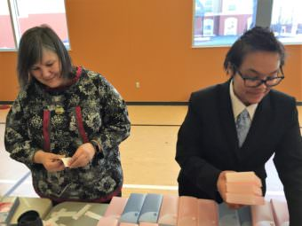"Department of Health and Social Services Commissioner Valerie ""Nurr'araaluk"" Davidson and Nichelle Willams pulls stickers off boxes with on a Narcan kit assembly line at Covenant House in March. (Photo by Anne Hillman/Alaska Public Media)"