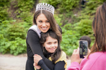 Miss Alaska USA Alyssa London poses with Juneau Community Charter School student Adrienne Whicker as her grandmother Alice Sollie takes their photo on Thursday, May 25, 2017, at Sandy Beach in Douglas.