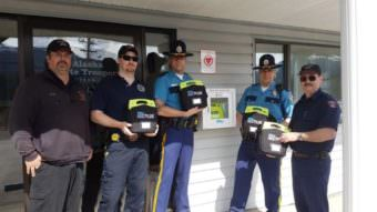 Members of the NTVFD and Alaska State Troopers installing AEDs.